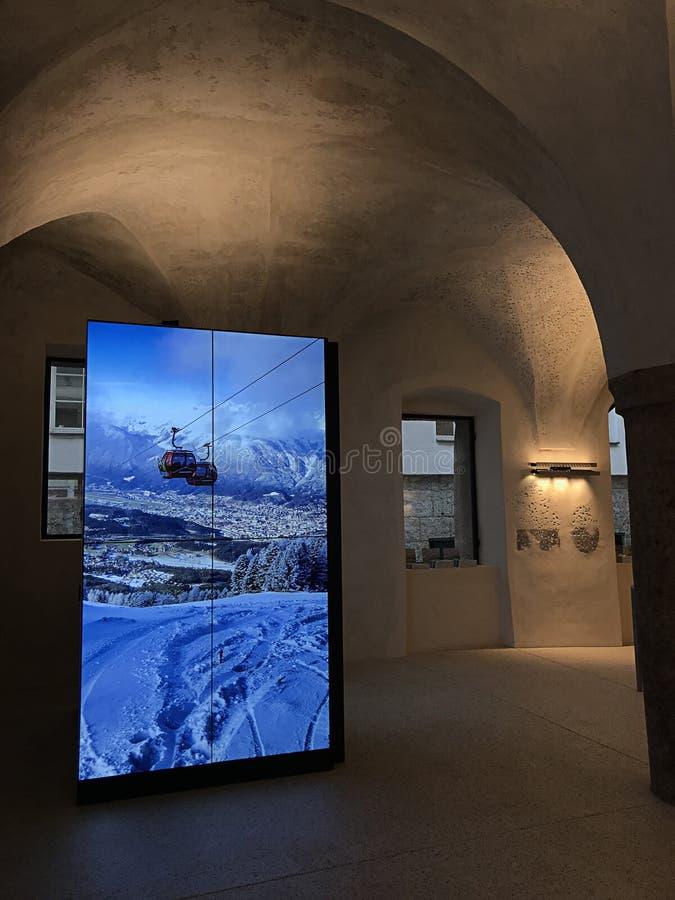 Bilden av kabelbilen som flyttar sig till och med de snöig bergen som visas på den stora skärmen av turist- information Innsbruck arkivbilder