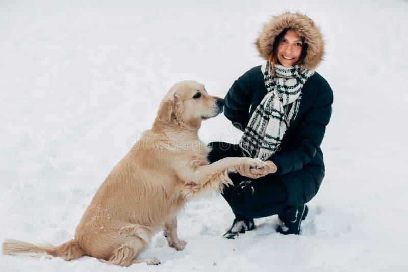 Bilden av labrador att ge sig tafsar till kvinnan i svart omslag på vinter arkivbilder