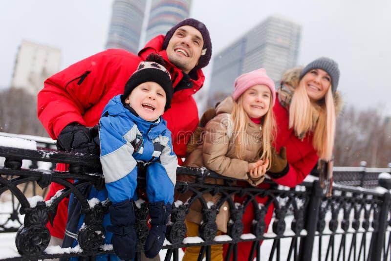 Bilden av lyckliga föräldrar med dottern och sonen på vinter går royaltyfria foton