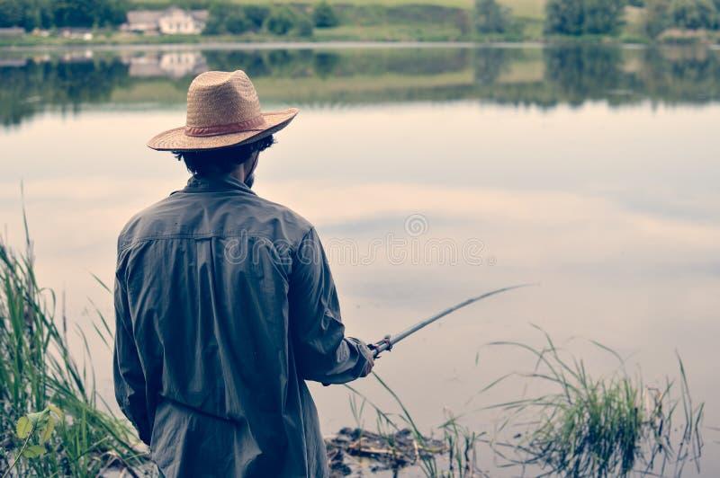Bilden av mannen som har bra tid- & gyckelfiske på banken på fridsamt vatten kopierar utomhus, utrymmebakgrund arkivbild