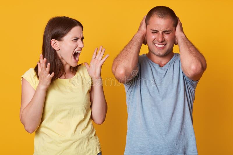 Bilden av par grälar, den irriterade ilskna munnen för skrikakvinnaöppningen brett och att lyfta hennes armar som ser maken Förar royaltyfri bild