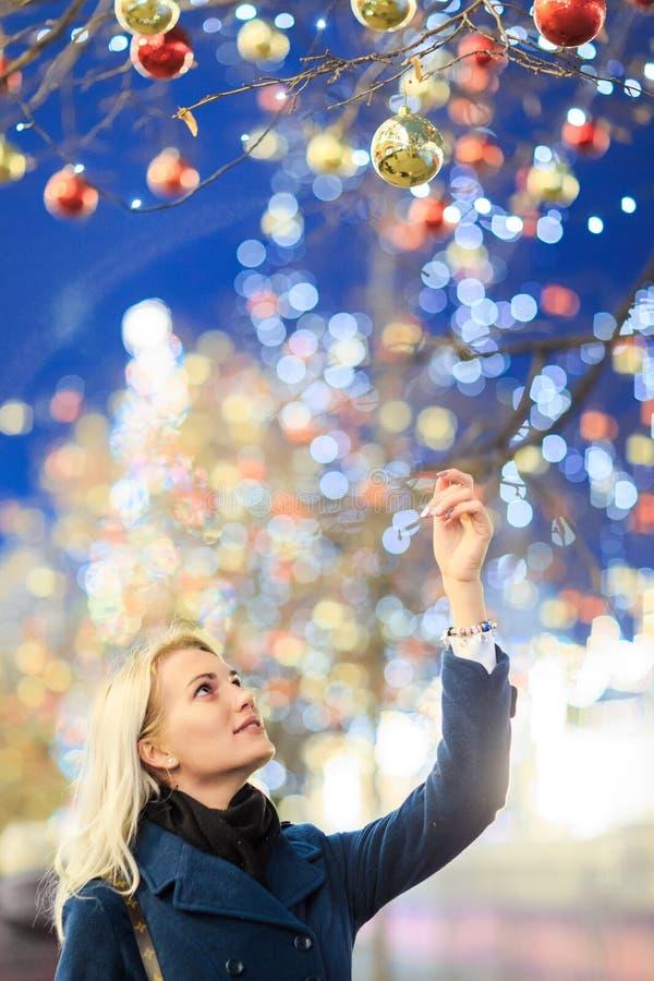 Bilden av rörande jul för den härliga kvinnan klumpa ihop sig på träd royaltyfria foton