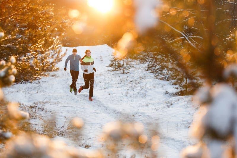 Bilden av rinnande sportkvinnor och män i vinter parkerar royaltyfria foton