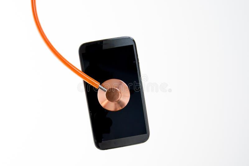 Bilden av stetoskopet och mobiltelefonen diagnostiserade modernt sjukdommedicinsk forskning- eller telefonreparations- och servic royaltyfria foton