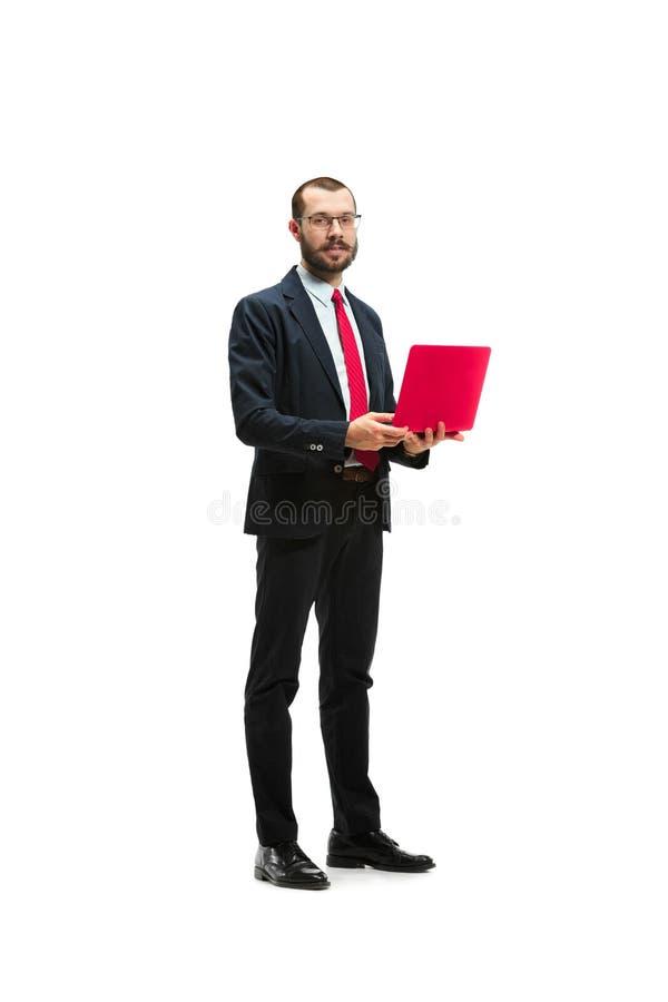 Bilden av stiligt barn uppsökte mannen som står över vit studiobakgrund med bärbara datorn arkivbild