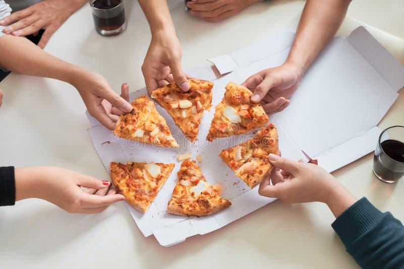 Bilden av tonårs- vänner räcker att ta skivor av pizza arkivbild