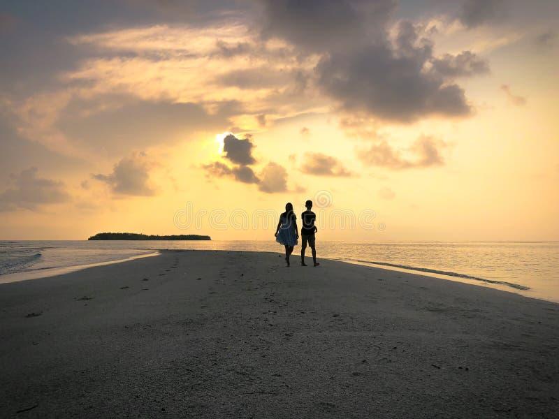 Bilden av två personer som är förälskade på solnedgången arkivbild