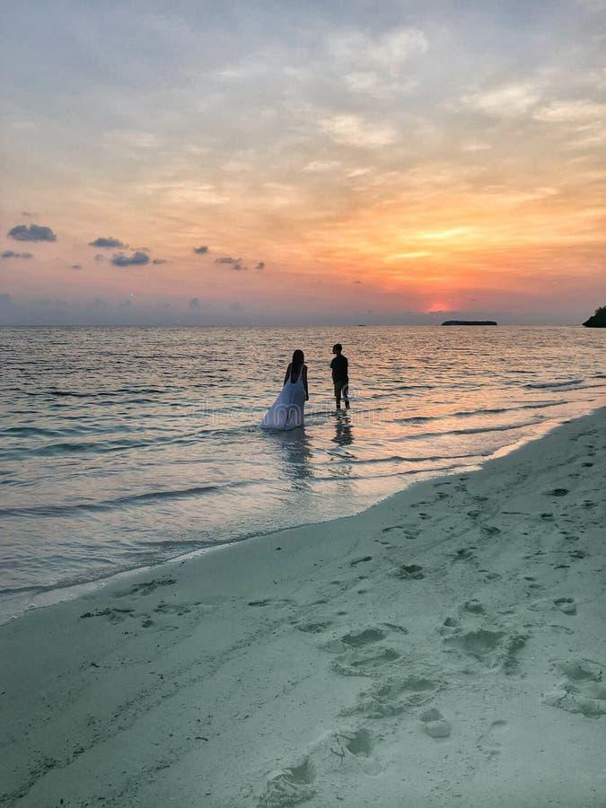 Bilden av två personer som är förälskade på solnedgången royaltyfria foton