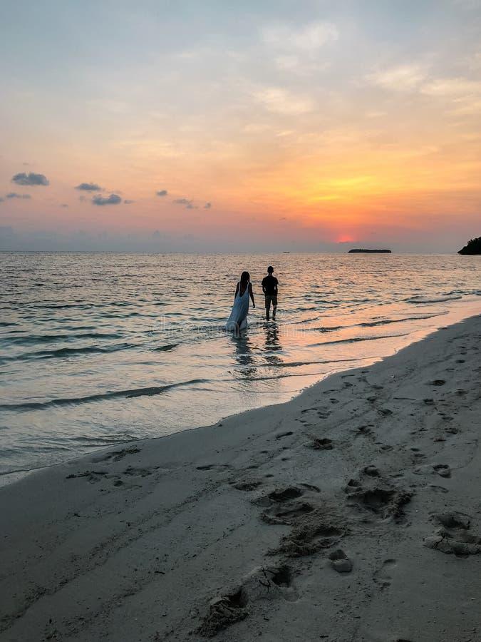 Bilden av två personer som är förälskade på solnedgången arkivfoto