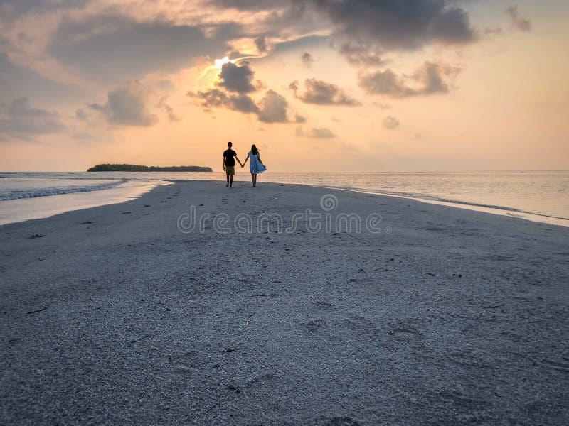 Bilden av två personer som är förälskade på solnedgången arkivfoton