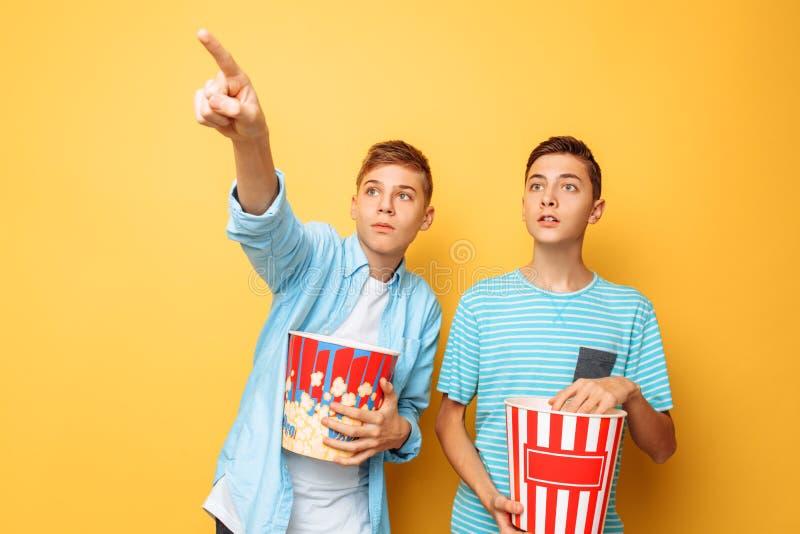 Bilden av två upphetsade härliga tonåringar, grabbar som håller ögonen på en intressant film och äter popcorn på en gul bakgrund arkivbilder