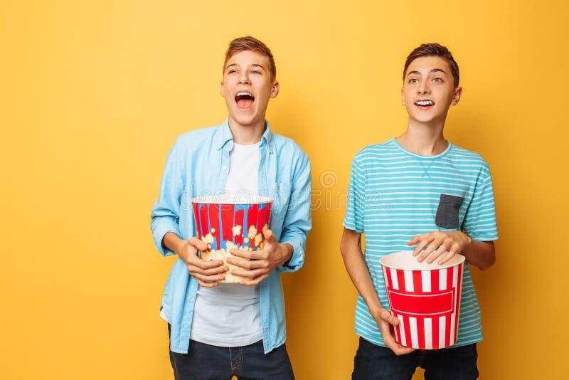 Bilden av två upphetsade härliga tonåringar, grabbar som håller ögonen på en intressant film och äter popcorn på en gul bakgrund royaltyfri bild