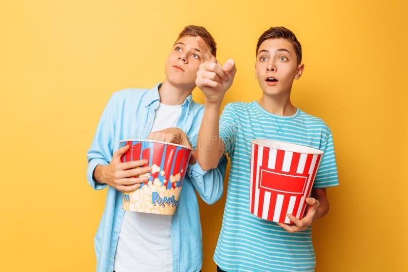 Bilden av två upphetsade härliga tonåringar, grabbar som håller ögonen på en intressant film och äter popcorn på en gul bakgrund royaltyfri fotografi
