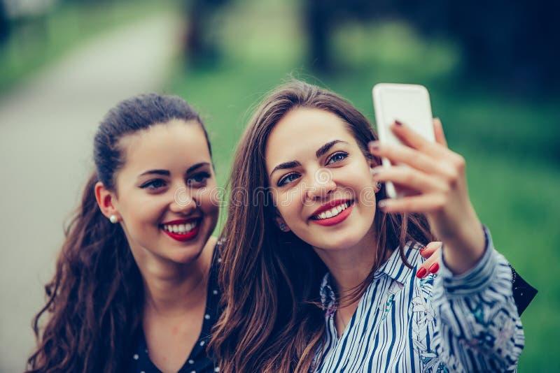 Bilden av unga härliga kvinnavänner, studenter som sitter i, parkerar gör selfie vid mobiltelefonen royaltyfria bilder