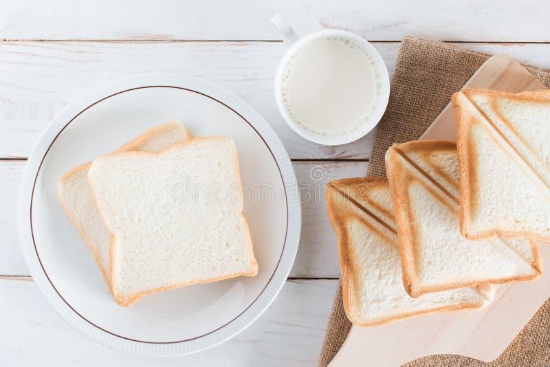 Bilden för den bästa sikten av Baked bröd och skivat bröd på skärbräda och maträtten med varmt mjölkar i den vita koppen på vit t royaltyfria bilder