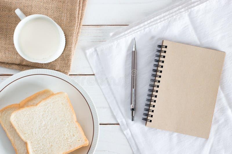 Bilden för den bästa sikten av Sliced bröd på maträtt med varmt mjölkar, ritar och den bruna pappers- anteckningsboken på vit trä arkivfoto