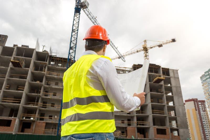 Bilden för den bakre sikten av den manliga arkitekten i hardhaten och västen som ser funktionsduglig byggnad, sträcker på halsen arkivfoton