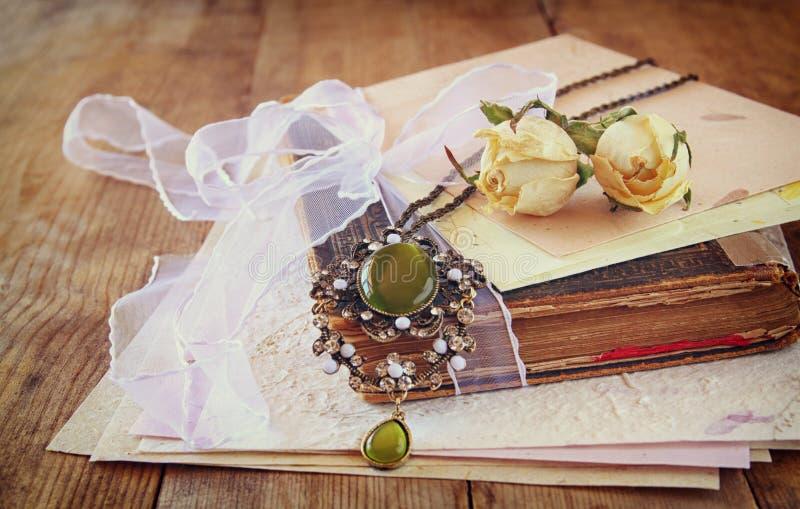 Bilden för den selektiva fokusen av torra rosor, den antika halsbandet och gammal tappning bokar på trätabellen retro filtrerad b royaltyfria bilder
