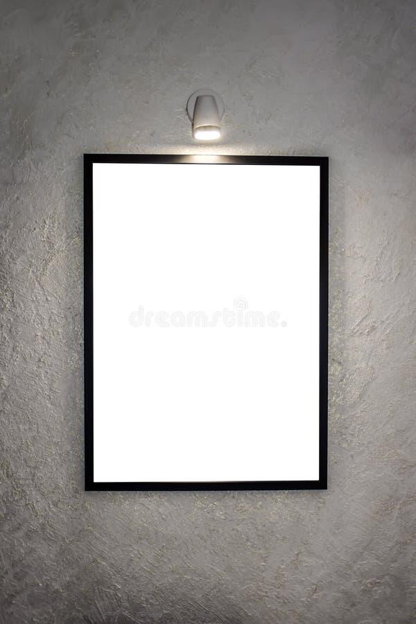 Bilden i en svart ram som hänger på väggen och exponerar av en lampa för målningar På bakgrunden av ett vitt arkivfoton