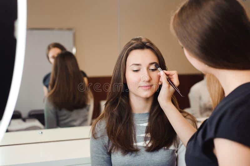 Bilden Sie den Künstler, der Fachmann tut, von der jungen Frau zu bilden Schönheitsschule lizenzfreies stockfoto