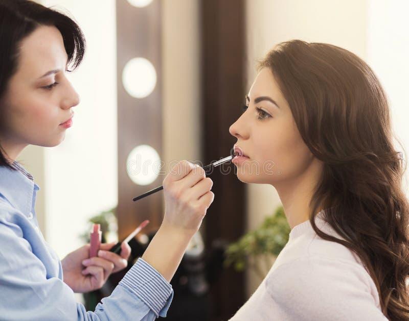 Bilden Sie den Künstler, der Glanz auf Frauenlippen im Salon anwendet stockfotos