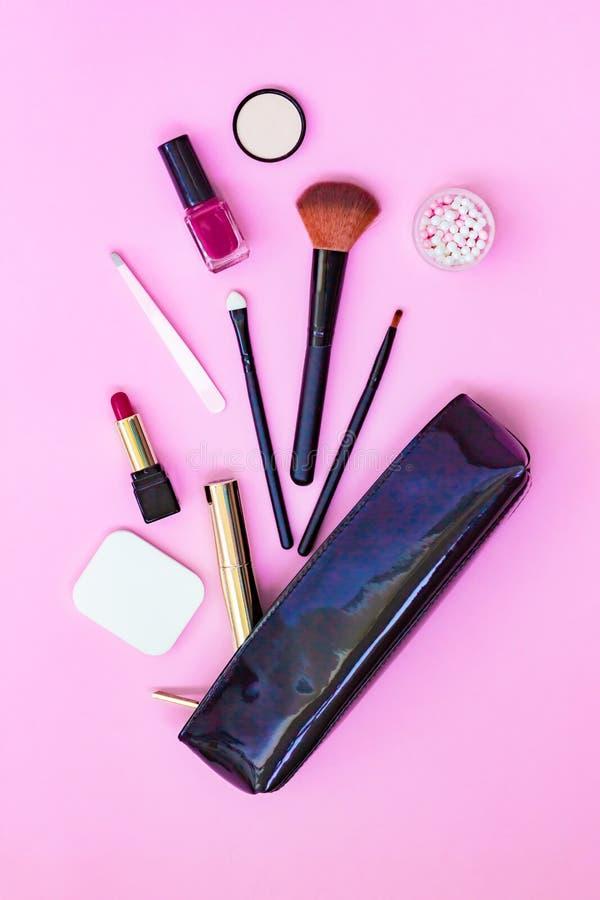 Bilden Sie die Produkte, die aus heraus schwarze lackierte Kosmetik verschüttet werden, sich bauschen auf einem rosa Pastellhinte lizenzfreies stockfoto