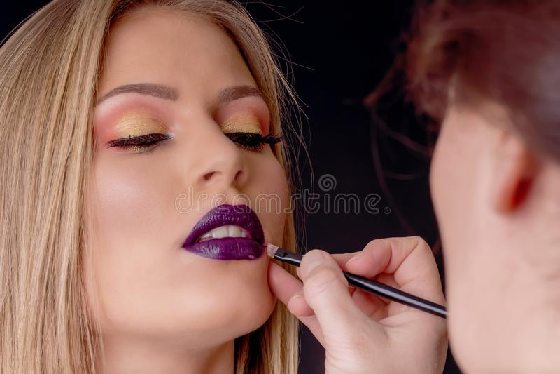 Bilden Sie im Prozess, Maskenbildner anwendet den Lippenstift und Lippe malen stockfotografie