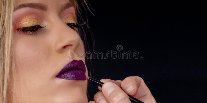 Bilden Sie im Prozess, Maskenbildner anwendet den Lippenstift und Lippe malen lizenzfreie stockfotos