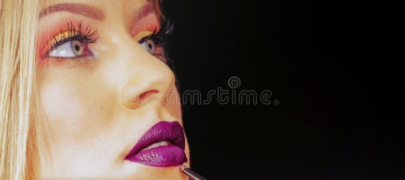 Bilden Sie im Prozess, Maskenbildner anwendet den Lippenstift und Lippe malen lizenzfreies stockfoto
