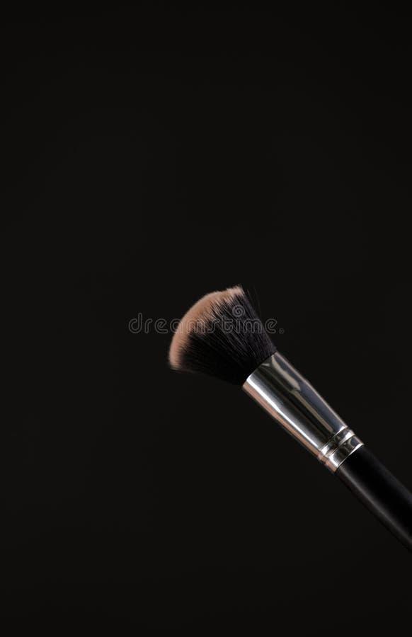 Bilden Sie kosmetische Bürsten mit Pulver, zu erröten Explosion auf schwarzem Hintergrund stockfotografie