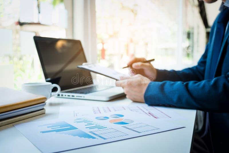 Bilder av affärsmannen som arbetar på kontoret med bärbara datorn och documen arkivfoton