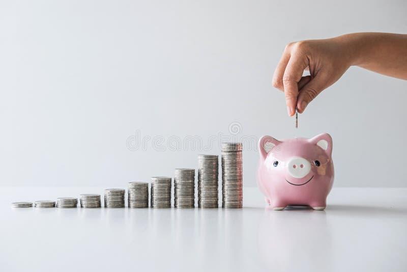 Bilder av att stapla mynt hög och hand som sätter myntet in i den rosa spargrisen för att planera moment upp till växa och bespar royaltyfri fotografi
