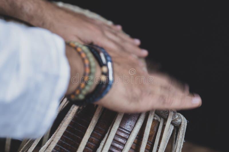 Bilder av en mans händer som bär pärlor som spelar Tablaen - royaltyfri foto