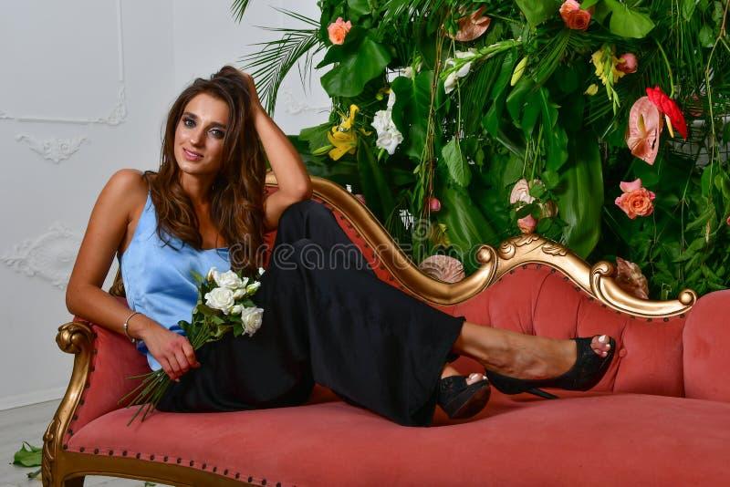 Bilder des schönen bezaubernden Mädchens auf der Retro- roten Couch und der Wand mit grünen Blättern und Blumen stockbild