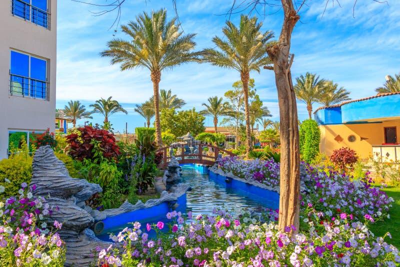 Bilder eines Wasserpools mit Brücke, Garten mit Blumen und dekorative Statuen stockbilder