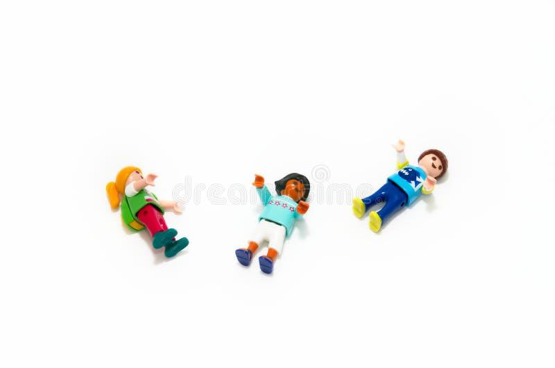 Bilder för leksaksbarn som spelar Isolerad på vit bakgrund De är tre figurer av olika raser och färger arkivbild
