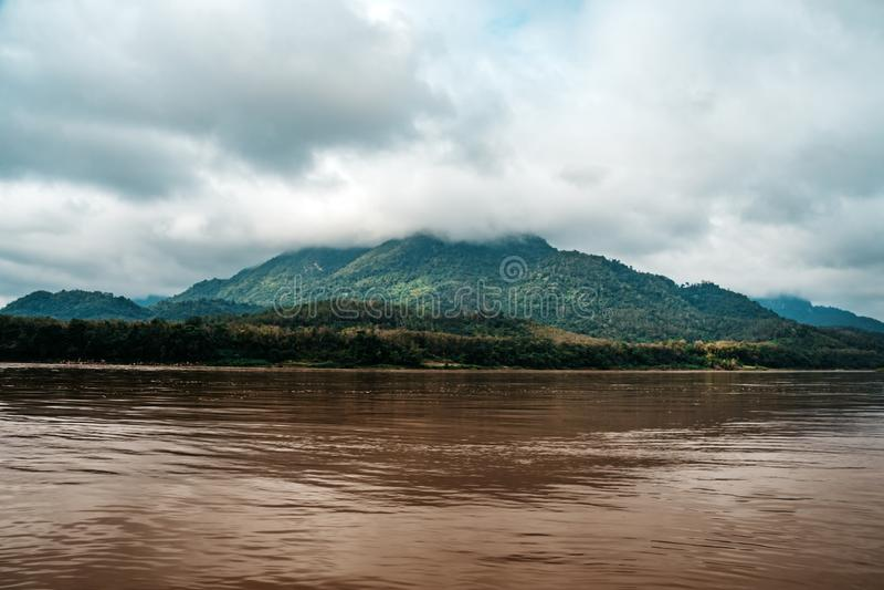 Bilder f?r ett landskap av kusterna av Mekonget River i s?dra Vietnam n?ra Vinh Long p? en solig sommardag Berg i moln royaltyfri foto