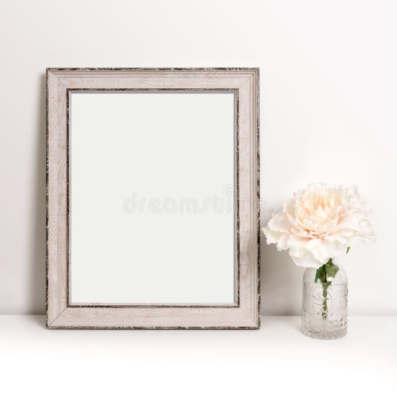 Bilderrahmenstellung auf Tabelle mit Blume in der dekorativen Flasche, Modell lizenzfreie stockbilder