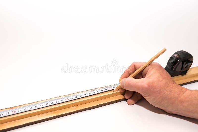 Bildframer, snickare som markerar ett långt stycke av bildramen med en blyertspenna arkivfoton