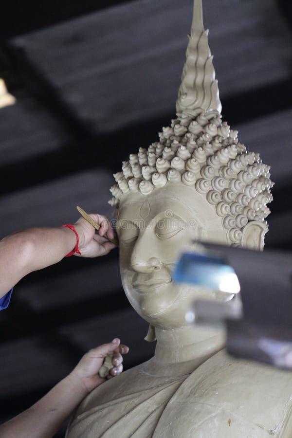 Bildhauerkünstler, der eine Fehlschlagskulptur mit Lehm, Hand von craftman Funktion auf Buddha-Statue, Nahaufnahmegesicht von Bud lizenzfreie stockfotografie