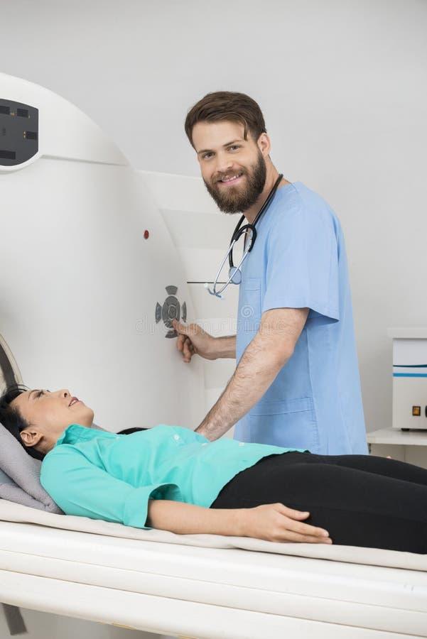 Bildläsning för barndoktor About To Start CT på kvinnlig patient royaltyfria bilder