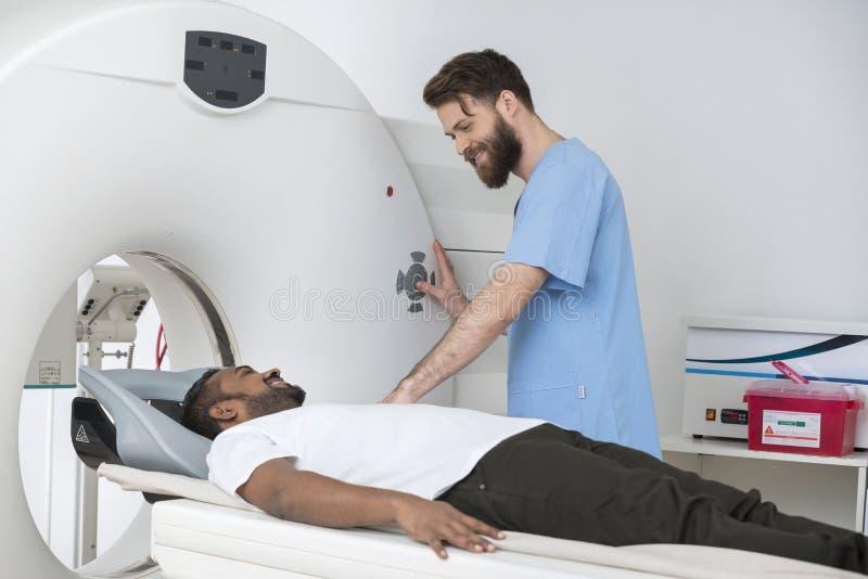 Bildläsning för barndoktor About To Start CT på man i sjukhus royaltyfria bilder