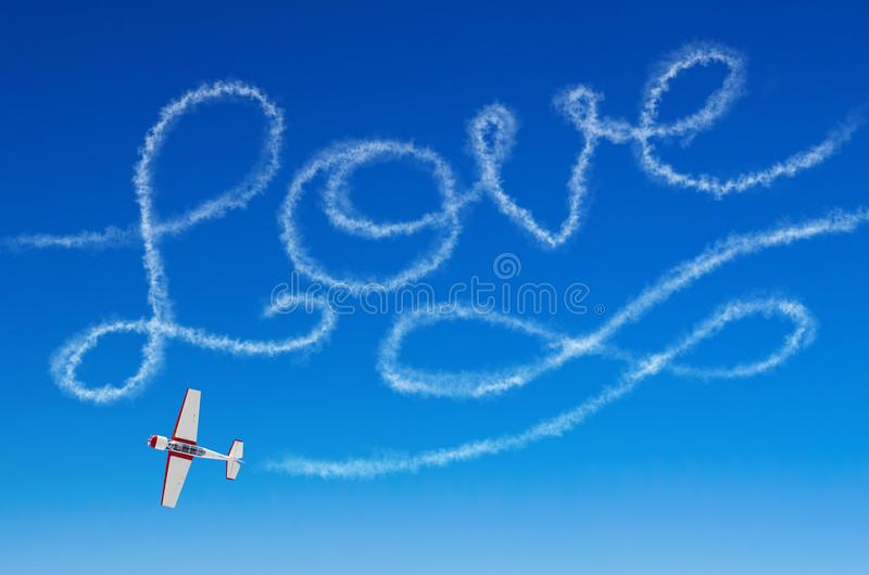 Bildliche Aufschrift der Liebe von einem weißen Rauchhinterflugzeug stockfoto