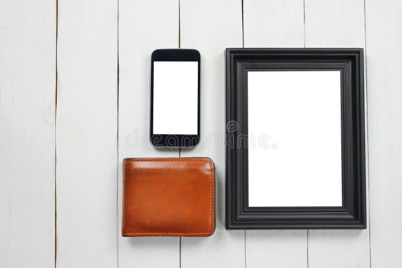 Bildram och smartphone och brun plånbok royaltyfri fotografi