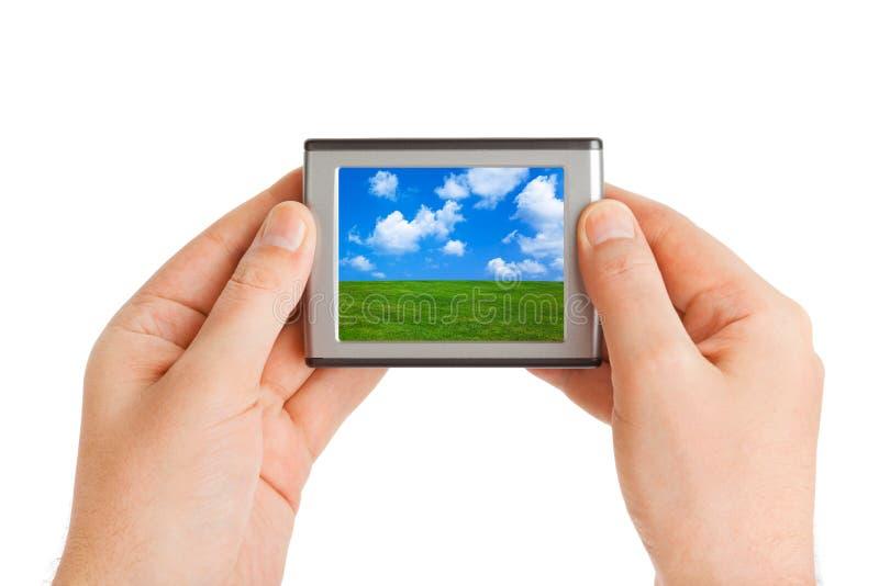 Bildschirm mit Landschaft (mein Foto) in den Händen stockfoto
