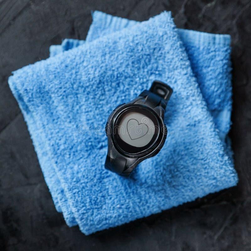 Bildskärm för hjärtahastighet på den blåa handduken nära fotbollboll royaltyfri foto