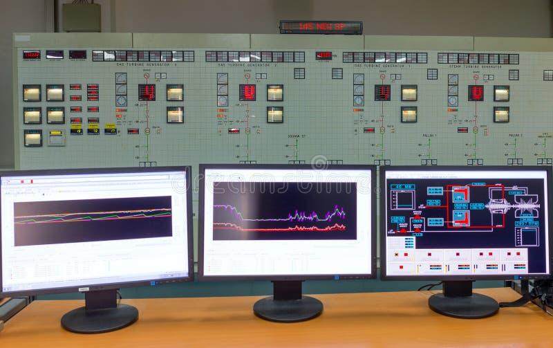 Bildskärmar i ett kontrollrum av en naturgaskraftverk arkivbilder