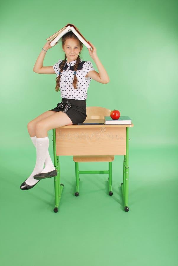 Bildung, Leute, Kinder und Schulkonzept - junges Schulmädchen, das auf Schreibtisch mit einem Buch auf ihrem Kopf sitzt lizenzfreies stockfoto