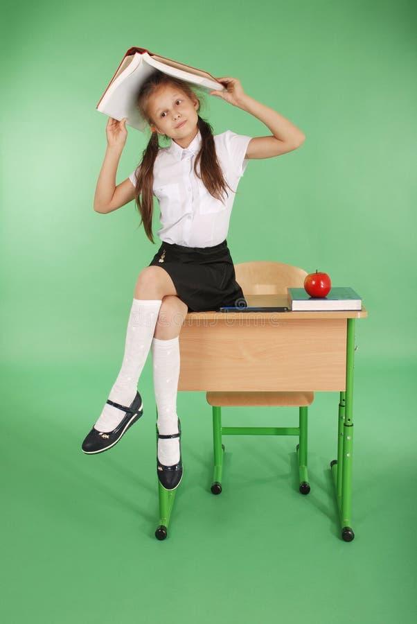 Bildung, Leute, Kinder und Schulkonzept - junges Schulmädchen, das auf Schreibtisch mit einem Buch auf ihrem Kopf sitzt lizenzfreie stockfotos