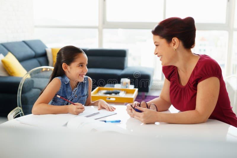 Bildung mit der Mutter-helfenden Tochter, die zu Hause Schulhausarbeit tut stockfotografie